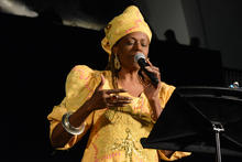 Linda Humes in a yellow dress and headpiece talking into a microphone