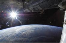 The sun rising over the top of Earth as seen from space