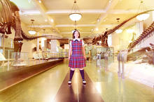 Young girl in a school uniform standing in an empty Hall of Saurischian Dinosaurs