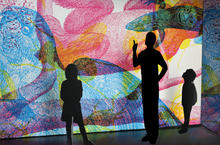 three silhouettes standing in front of a screen of colorful patterns