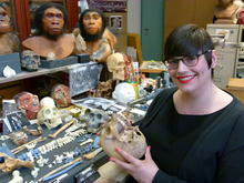 Claudia Astorino holding a human skull with an array of hominid fossils and 2 artistic hominin bust reconstructions behind her