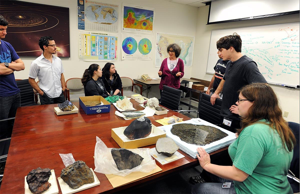 Teacher and students observing various rock specimens in a classroom