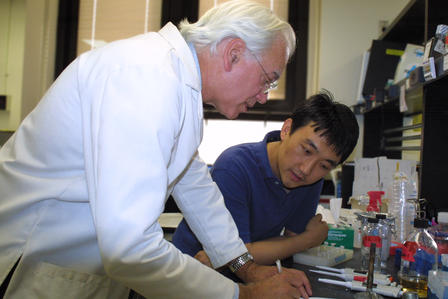A man in a white lab coat writing, while another man watches on.