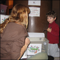 Tara DePorte of the Lower East Side Ecology Center introduces a young Museum visitor to worm composting