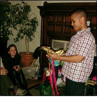 Photo of young man opening a gift at a holiday gift swap