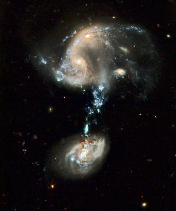 "Interacting Galaxies Group Arp 194 contains several galaxies, along with a ""cosmic fountain"" of stars, gas, and dust that stretches over 100,000 light-years. NASA, ESA, and the Hubble Heritage Team (STScI/AURA)"