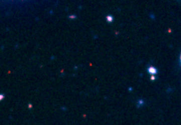 The afterglow of GRB 090429B (red dot, center) stands out in the in this optical and infrared composite from Gemini Observatory images. The red color results from the absence of visible light, which has been absorbed by hydrogen gas in the distant universe. Credit: Gemini Observatory/AURA/Andrew Levan (Univ. of Warwick, UK)