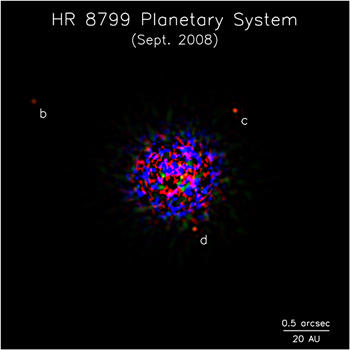 Three planets (red dots) are clearly in orbit around the star HR 8799. The speckled area is light from the star. An optical technique that sharpens the image allowed the planets to come into view. Image: Marois, et. al, Keck Observatory, National Research Council Canada