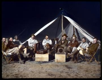 Expedition group seated, enjoying Victrola, Third Asiatic Expedition, Gobi Desert, Mongolia. (AMNH image no. LS3-07)