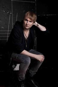 Photo of DJ Travis Stewart, known as Machinedrum, seated, wearing black clothes and leaning forward