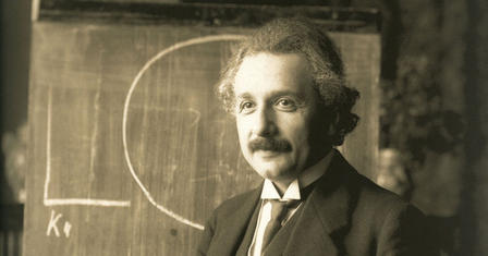 A sepia-toned photograph of Albert Einstein in front of a chalkboard