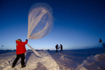 NOAA staff at the South Pole release a high-altitude balloon that carries ozone-measurement equipment.