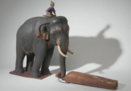 antique figurine of elephant in its traditional role as logger