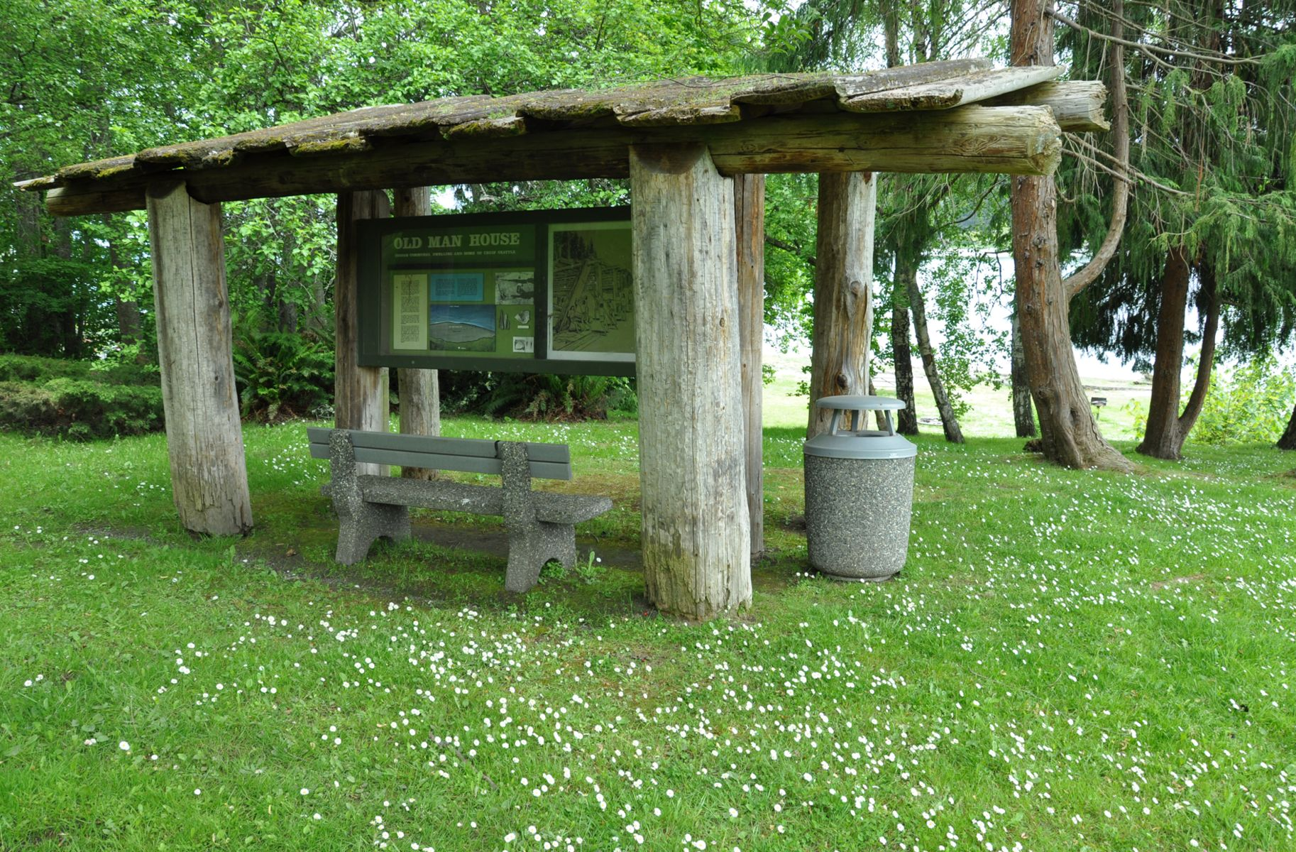 Open-sided timber shelter houses a bench and park information.