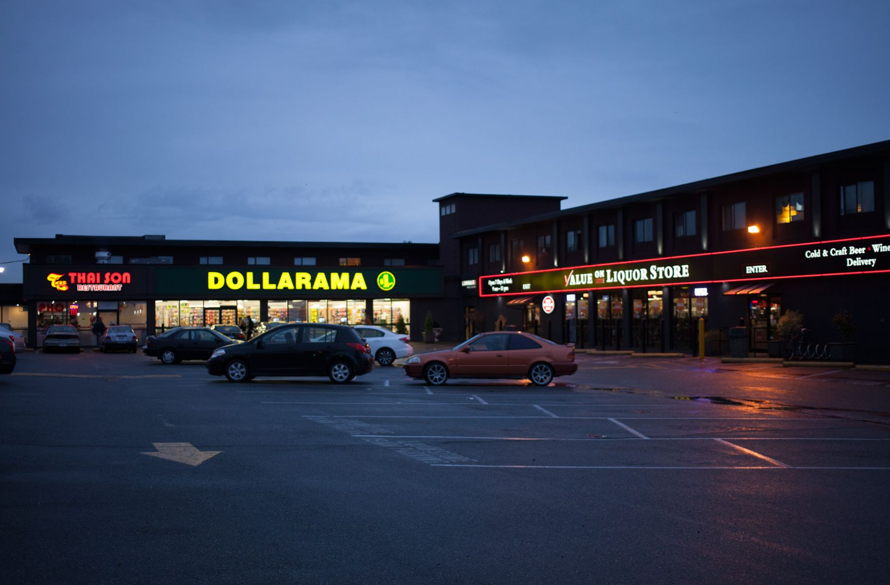 Parking lot at dusk, lit by the neon lights of surrounding stores, like Dollarama.