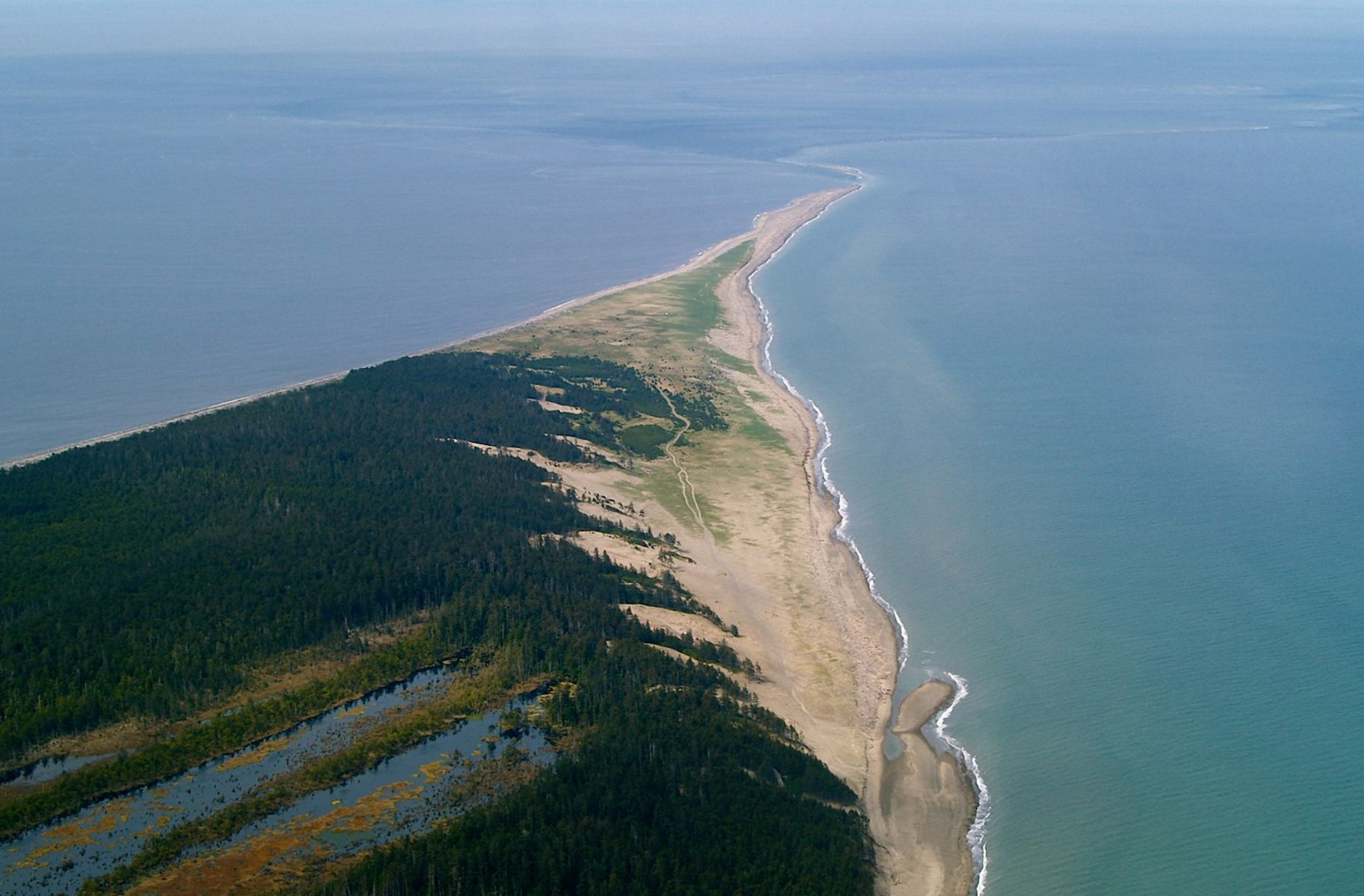 Aerial view of a spit of land stretching out into the water.