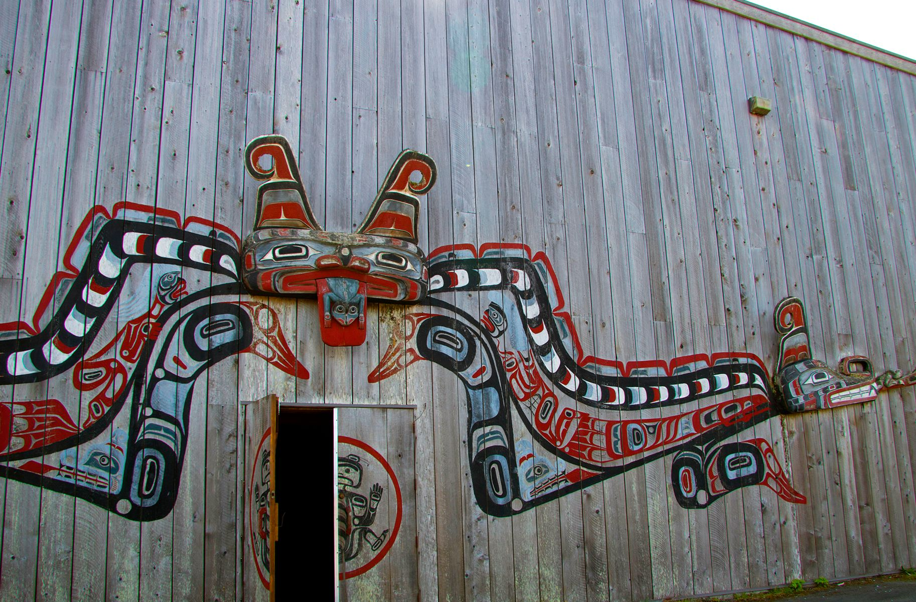 Wood plank building with a double-headed serpent painted over the doorway.