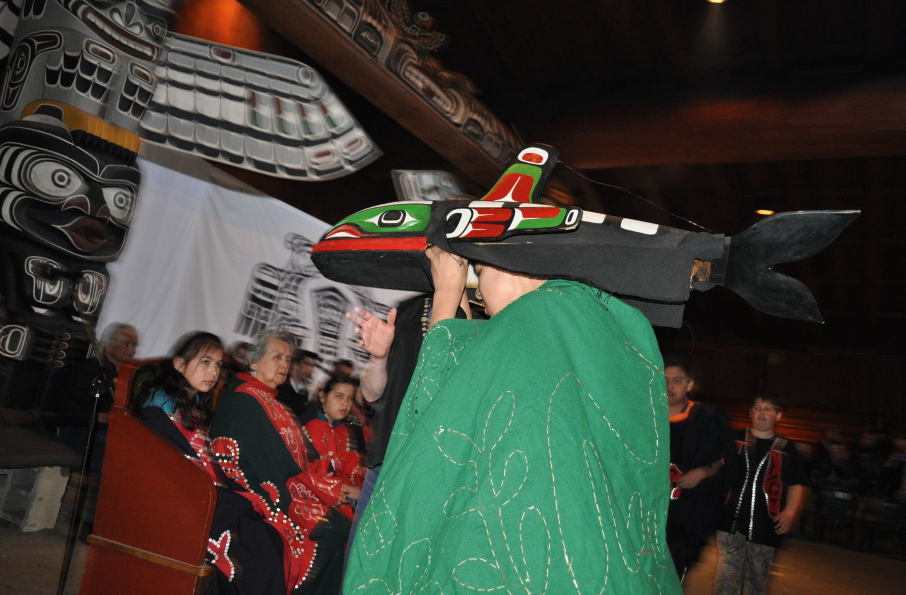 Man wearing a headdress addresses a group of people.