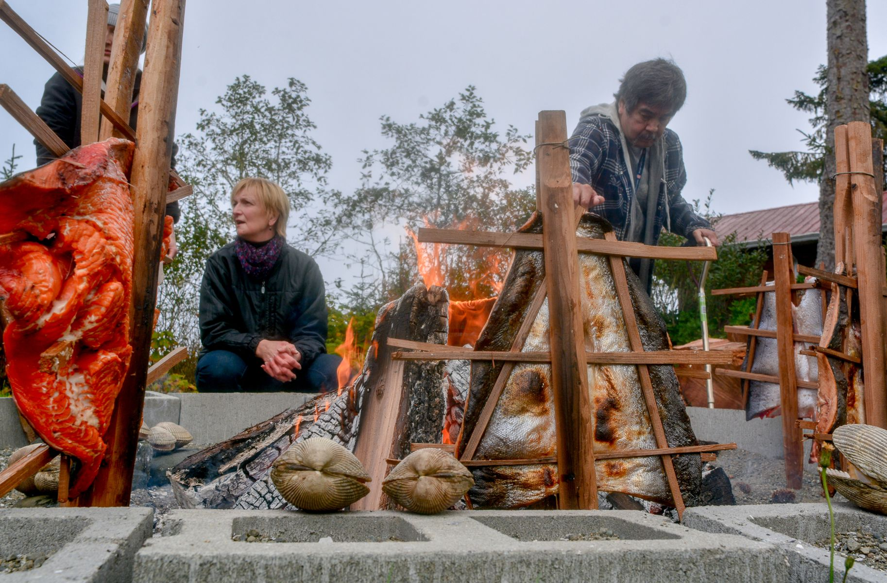 Two people prepare food outdoors over open fires.