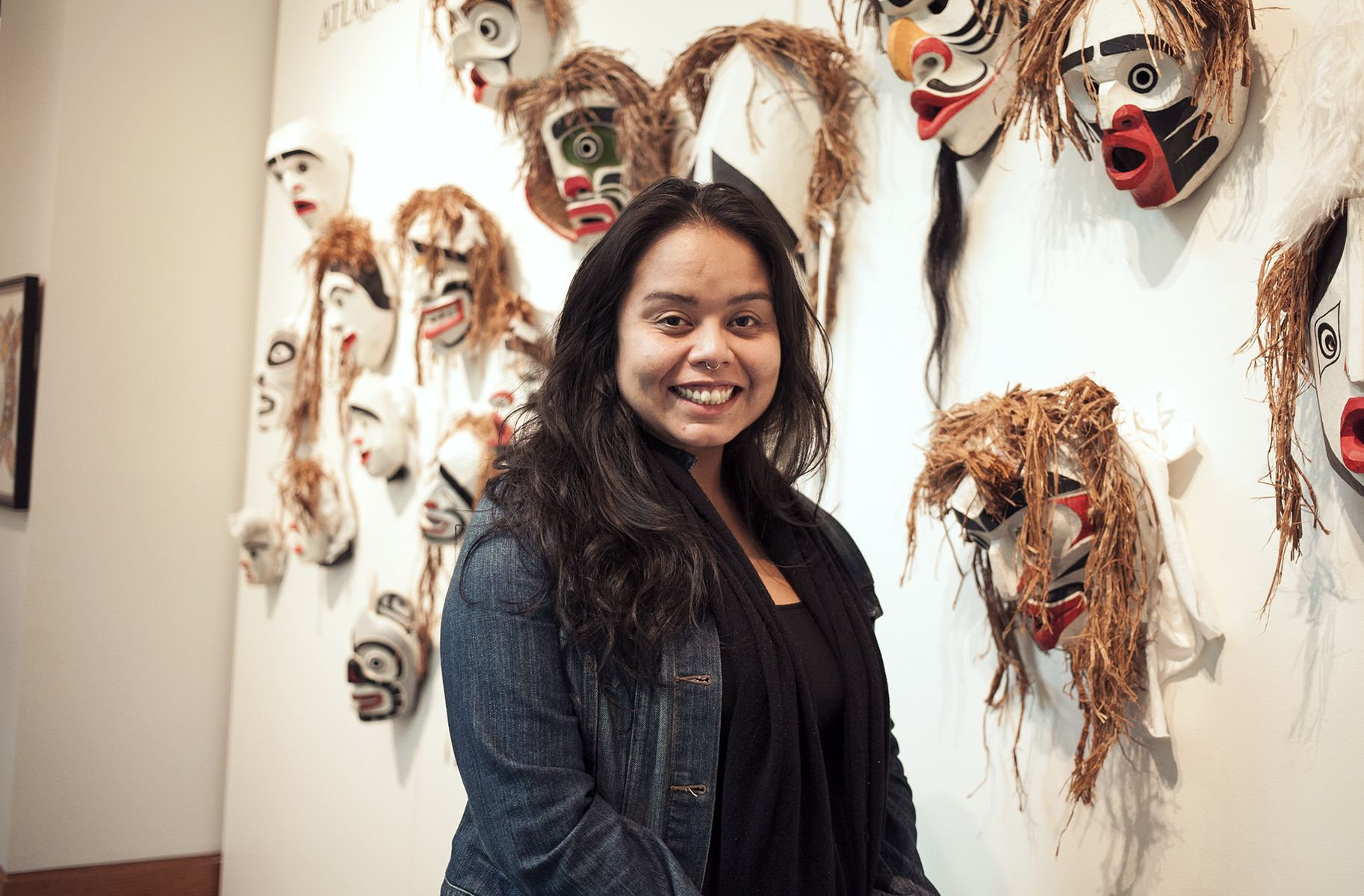 Smiling woman stands in front on which masks and headdresses are displayed.