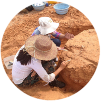 Two researchers in large hats clean a large round red sandy mound with brushes.