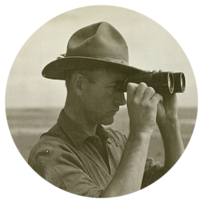Roy Chapman Andrews stands next to a camel and looks through binoculars at the desert landscape.