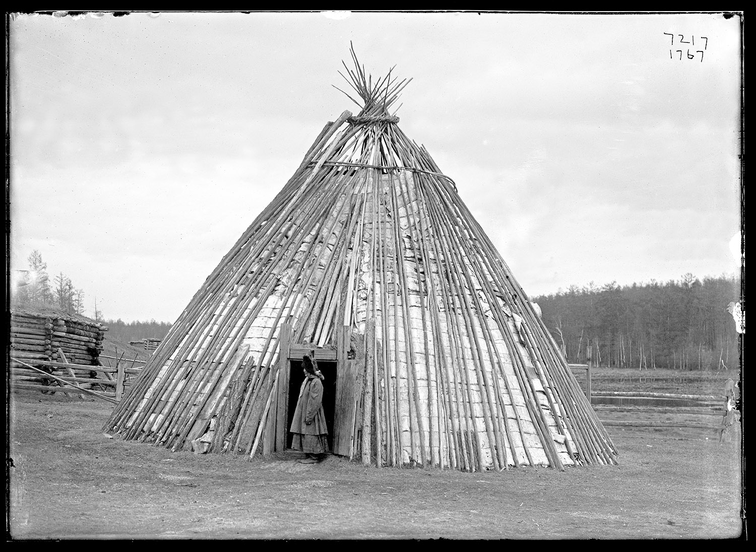 Person stands in the entrance of a conical, tipi-like structure constructed of reindeer hides and wooden poles.