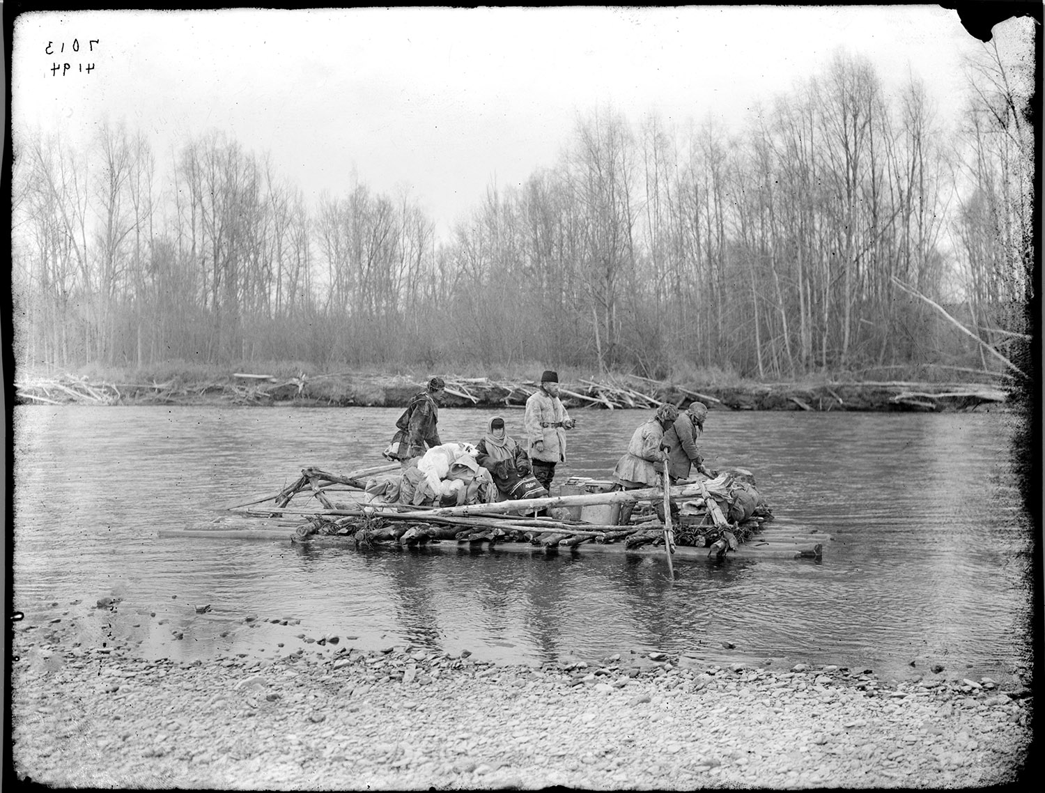 Five adults, a dog and packs of equipment are being carried downstream aboard a raft made from logs and branches tied together.