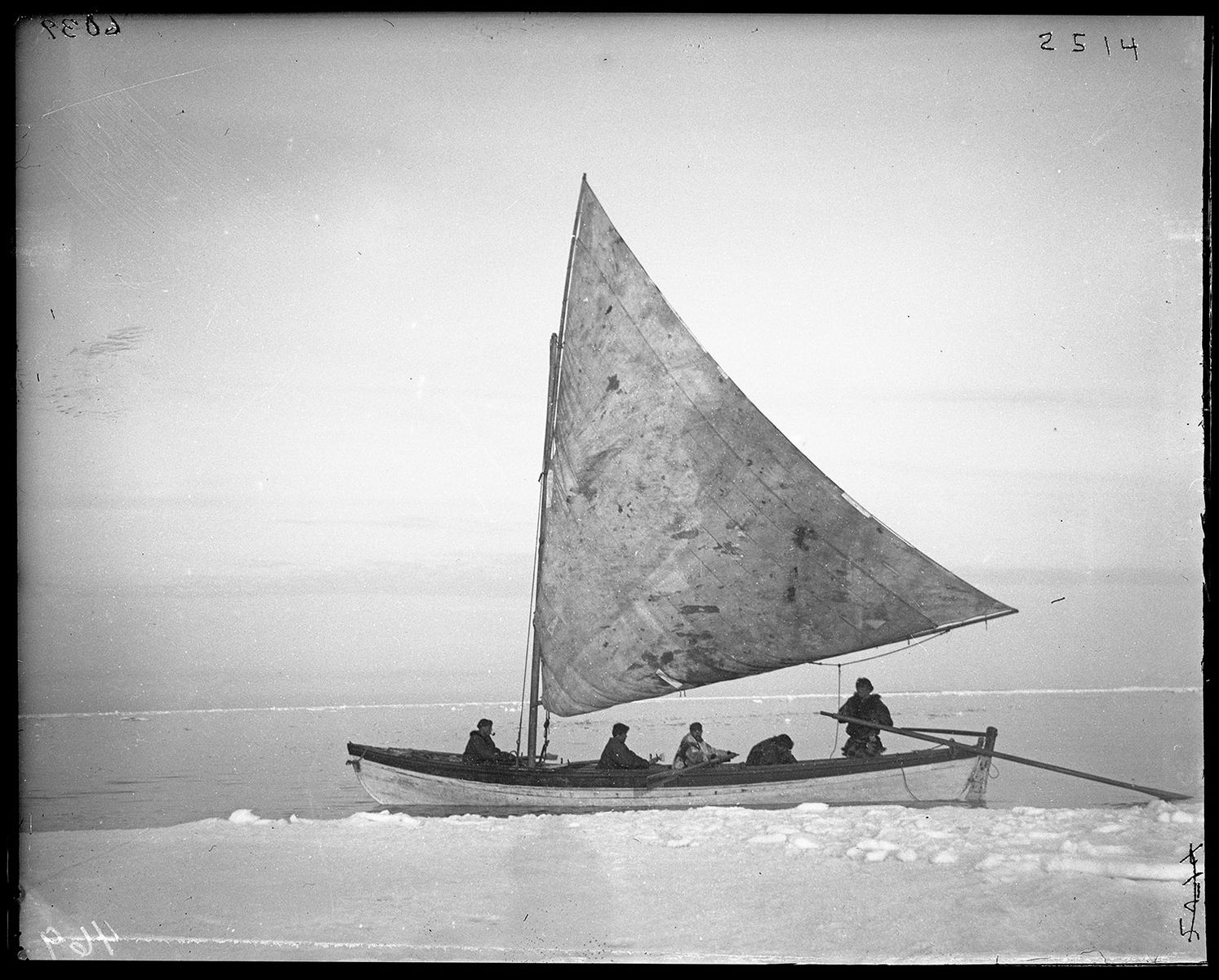 A small single sail boat carrying 5 people makes it's way across icy waters.