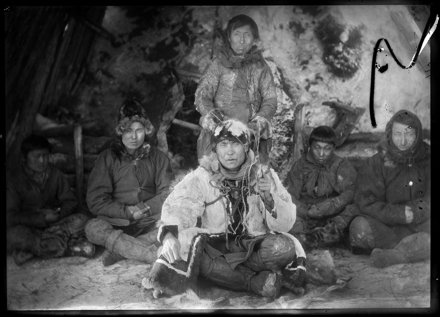 Yakut man dressed in decorative robes and headgear is seated on the ground in front of five other yakut men.