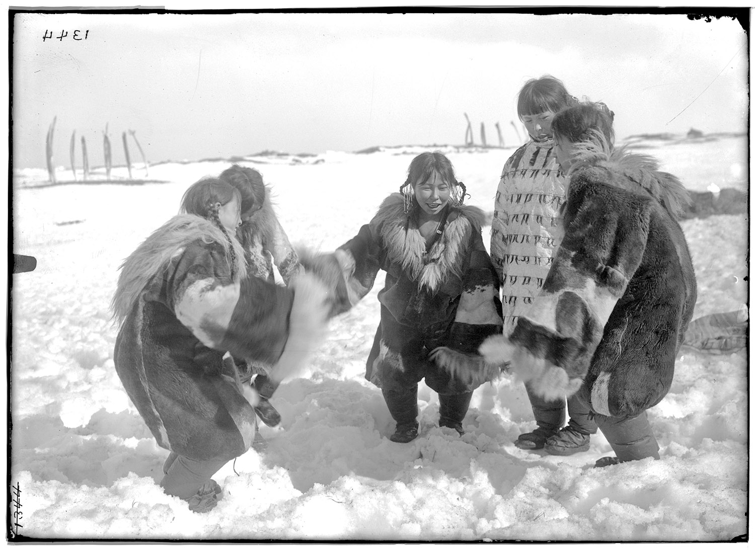 Five women wearing heavy garments hold hands in a circle and dance in the snow.