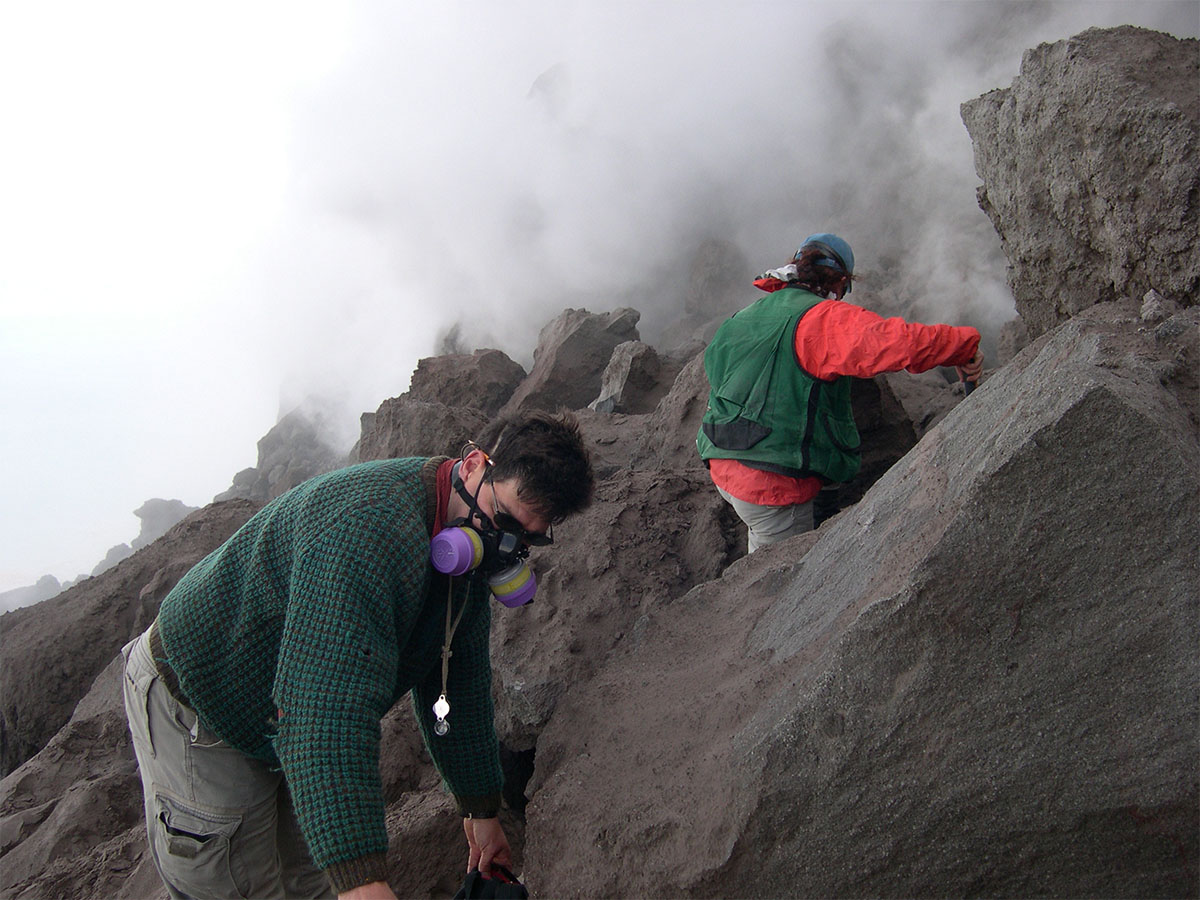 Volcanologist wearing mask and team member amid rocks and smoke.