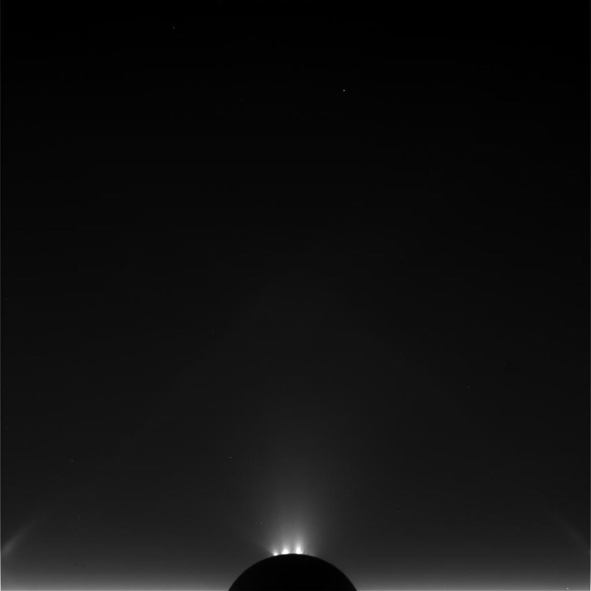 Dark silhouette of Saturn's moon in space, with glowing, cold jets visible above the surface.