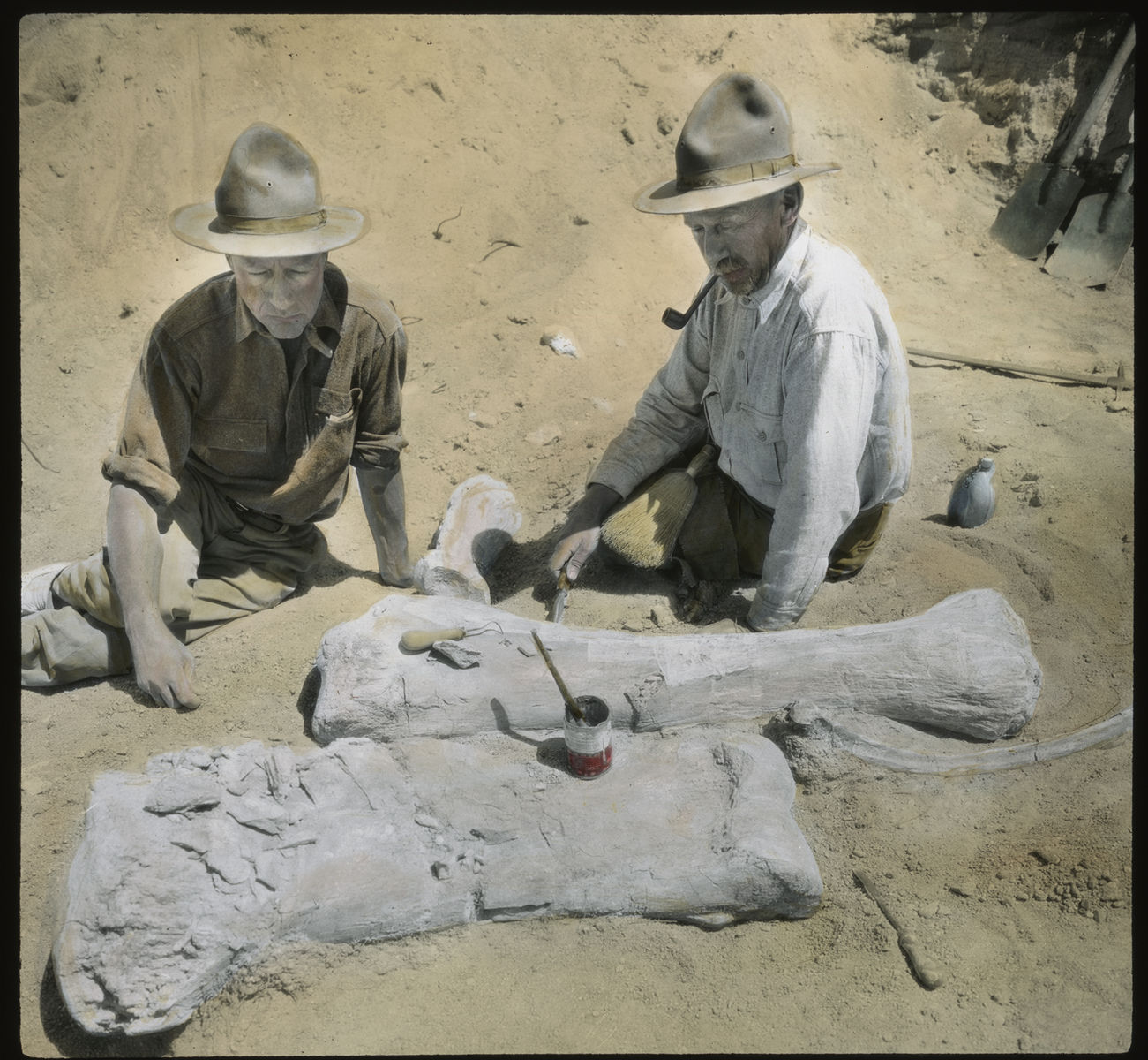 Two men in field gear, one with a pipe, sit on the ground with unearthed fossils.