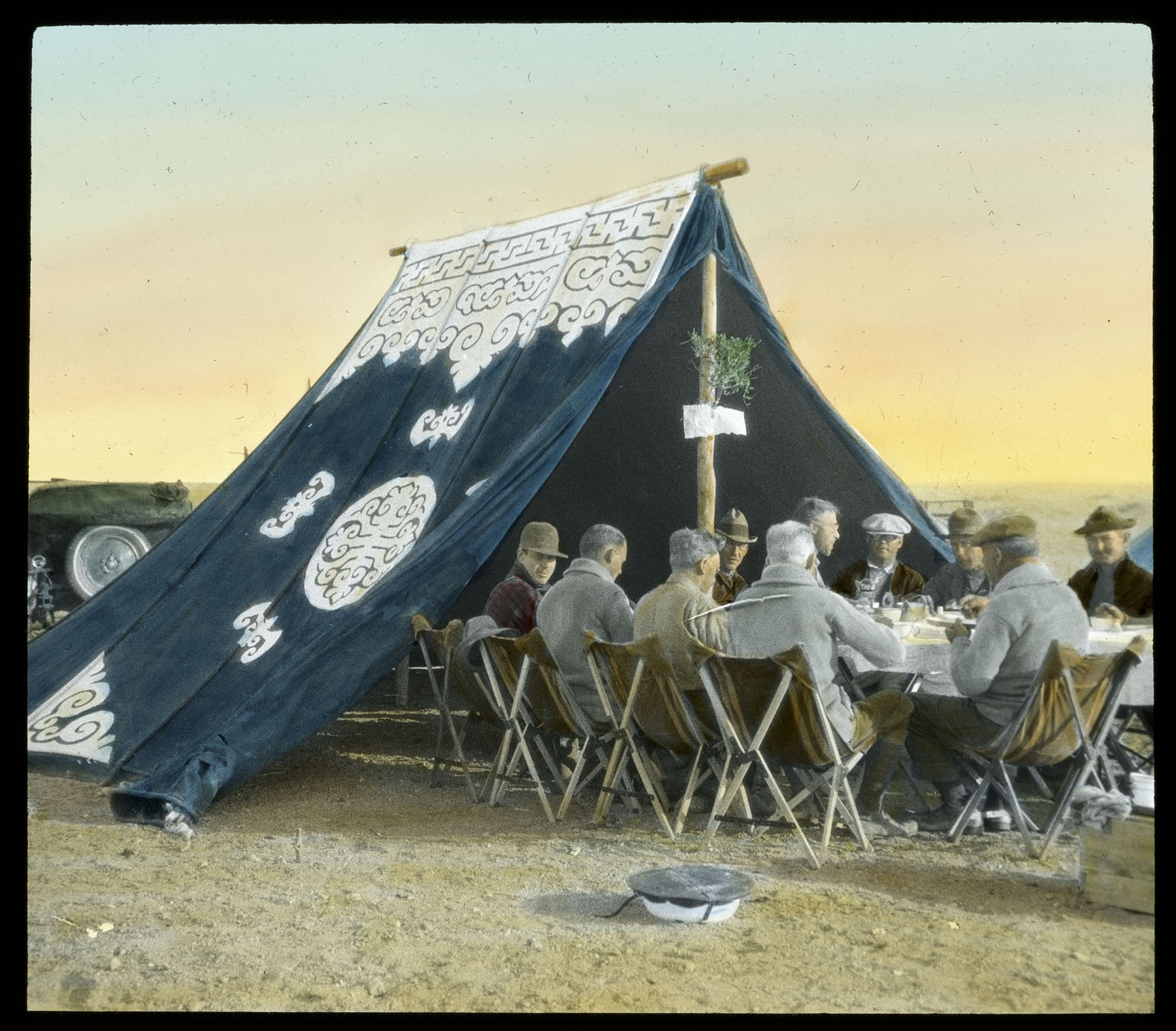 Expedition participants sit at a dining table that extends out of a tent on a 1920s expedition to the Gobi.