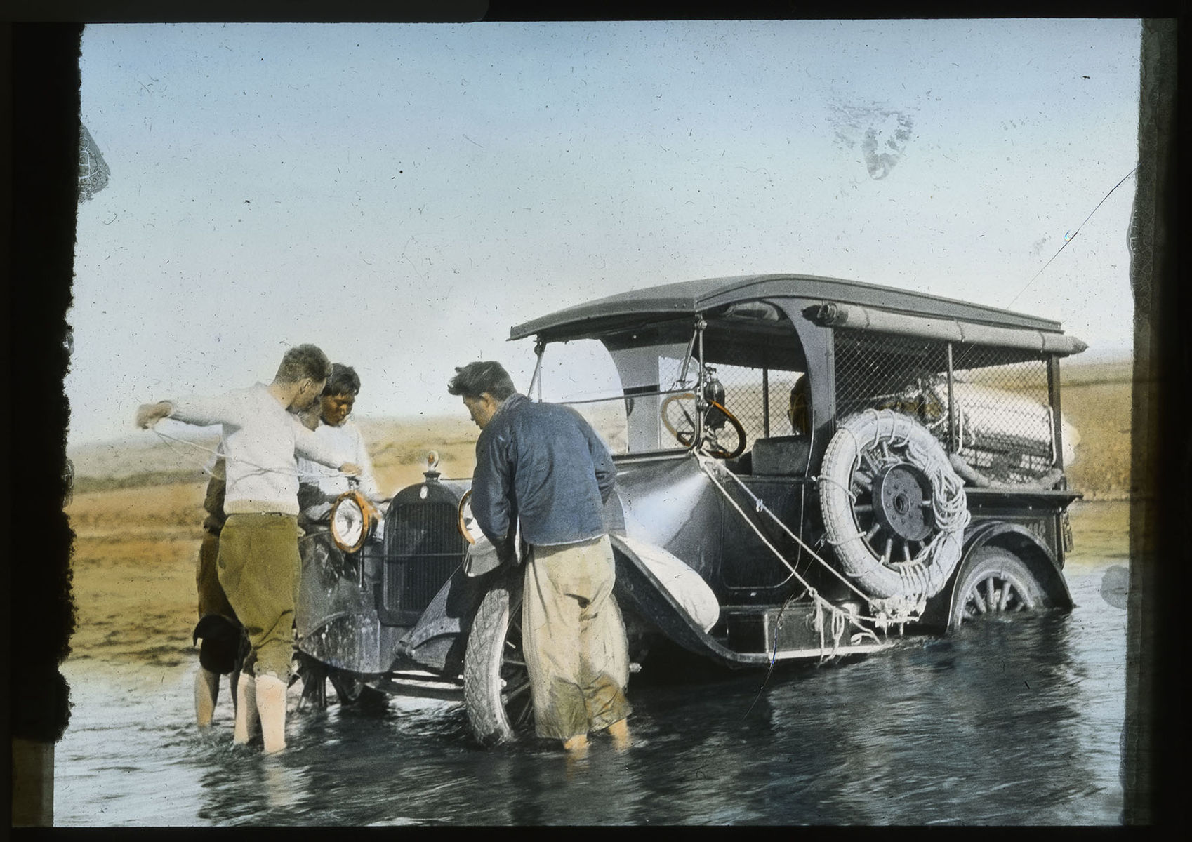 Expedition members gather around a car that has driven into low water.