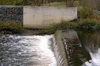 The stream crosses a man-made barrier